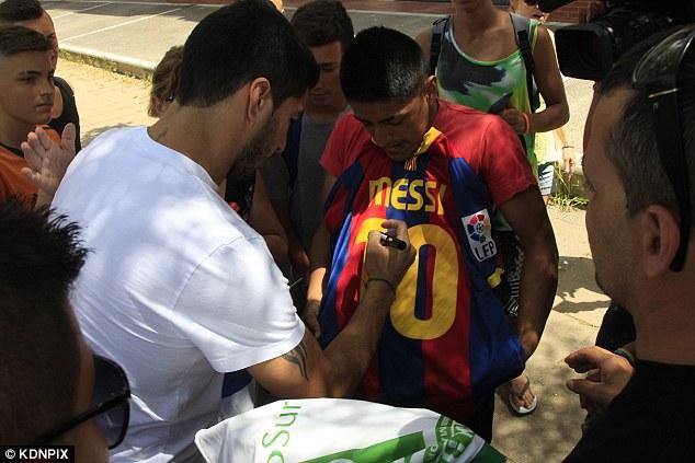 Luis Suarez signs Messi shirt