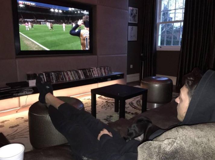 Mesut Ozil watching Arsenal on TV with Balboa the pug