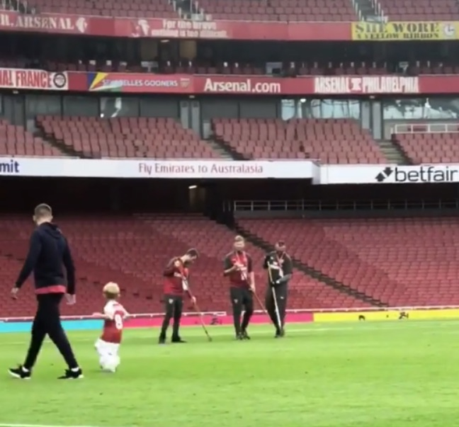 Aaron Ramsey (left) watches as his son plays on the Emirates pitch